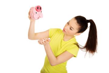Unhappy woman shaking piggybank.