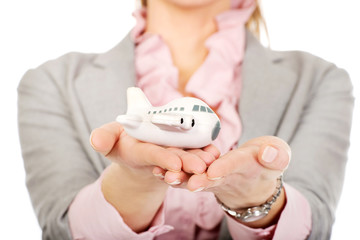 Business woman holding an airplane model.