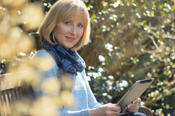 smiling mature woman with a tablet pc sitting in the garden