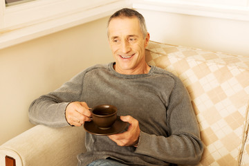Casual man sitting on couch drinking coffee