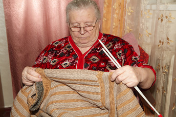 Old woman and knitting sweater