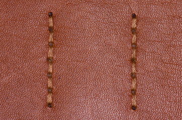 Brown stitched leather close-up. Two vertical seams