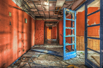 Blue door in red dilapdated corridor at an abandoned hotel