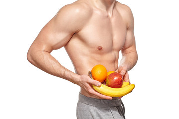 Fit young man with beautiful torso holding fruit