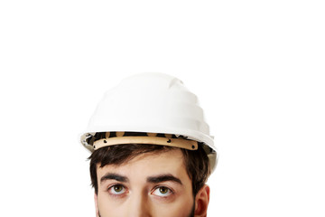 Young man with hard hat looking up.