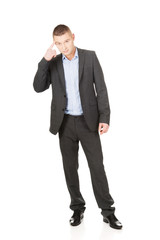 Businessman gesturing with finger against temple