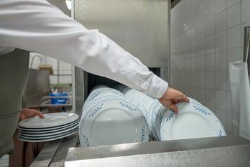 bulaşık makinasından tabak alan görevli