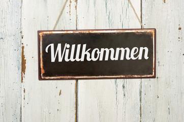 Altes Blechschild vor weißer Holzwand - Willkommen