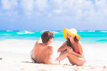 back view of couple sitting on beach