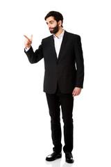 Happy businessman points his finger.
