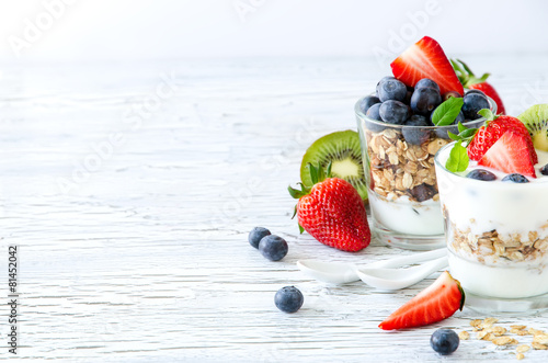 Healthy breakfast with muesli in glass, fresh berries and yogurt