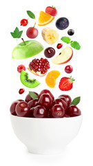 Falling fresh fruits and berries in bowl
