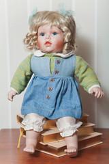 Vintage porcelain doll blonde sitting on stack of books