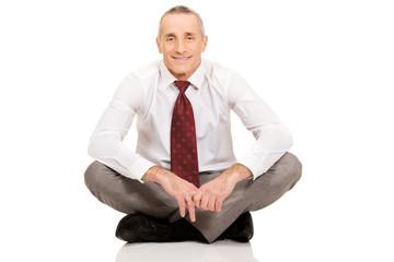 Businessman sitting cross-legged on the floor