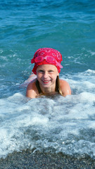 Little girl swimming in the sea and playing in the coastal strip