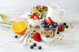 Healthy breakfast with muesli in glass, fresh berries and yogurt