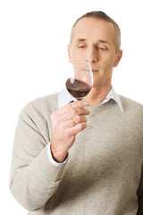 Mature man tasting red wine