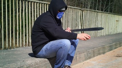 Man sharpens the machete on the bridge