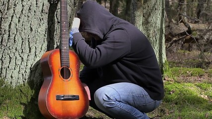 Stressful Man with guitar in the forest near tree