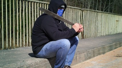 Man with machete on shoulder on the bridge