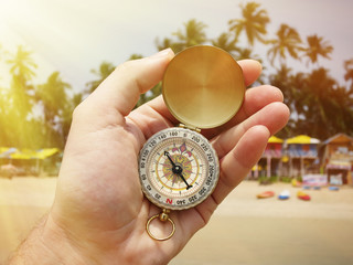 Compass in the hand against Palolem beach. South Goa, India
