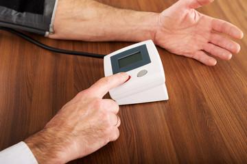 Closeup on businessman measuring blood pressure