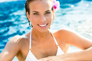 Brunette smiling woman relaxing in pool, summer vacation concept