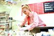 junge Mitarbeterin an Theke im Supermarkt füllt Speisen ab