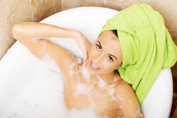 Woman relaxing in bath looking at camera