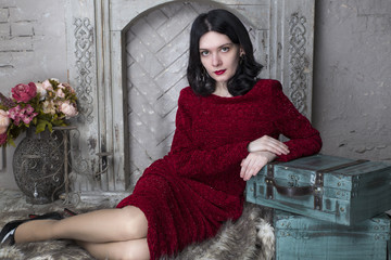 Brunette young woman in red dress sitting near the fireplace