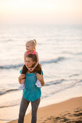 Happy baby girl sitting on shoulders of mother on beach