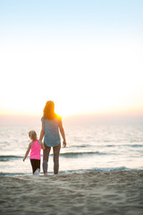 Healthy mother and baby girl walking on beach in the evening
