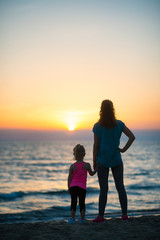 Silhouette of mother and baby girl on beach