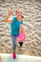 Portrait of healthy mother and baby girl on beach pointing