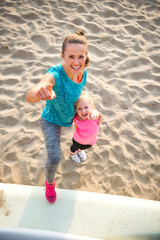 Portrait of healthy mother and baby girl pointing while on beach