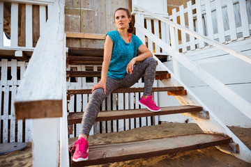 Fitness young woman sitting on stairs of beach house