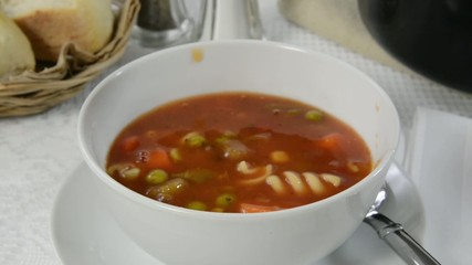 Ladling vegetable soup into a bowl