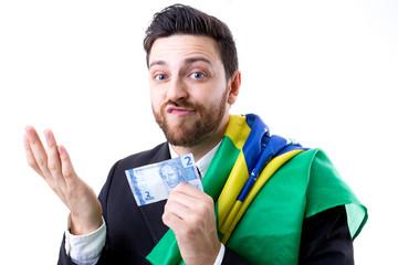 Brazilian not so happy holding Brazilian money and the flag