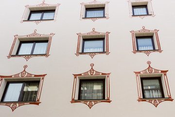 squared glass windows with brown frame and artistic border with