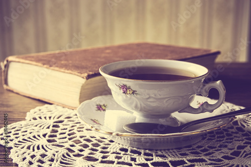 Fotobehang Thee Cup of tea with book on napkin vintage effect