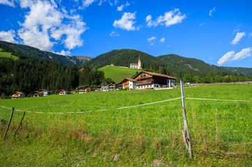 Green meadow and alpine houses in Strassen village, Austria
