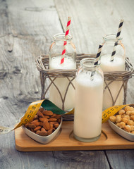Different vegan milks on a table. Substitute for dairy milk.