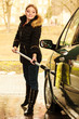 Woman washing car on open air