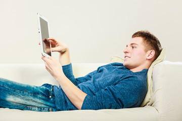 Young man with digital tablet laying on couch