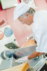 Butcher slicing some ham