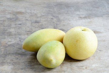 Chinese pear and Ripe Mangoes on wooden background