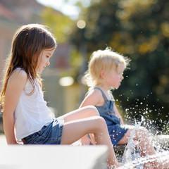 Little sisters having fun in a fountain