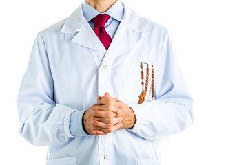 Doctor in white coat holding wooden Rosary beads in pocket
