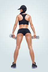 Fitness sporty woman pumping up muscles with dumbbells