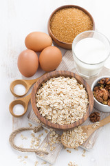 oat flakes and ingredients on a white wooden table, vertical